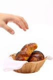 Main au-dessus des croissants dans le panier. Photos stock