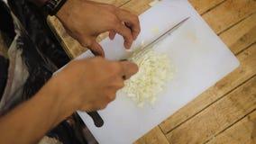 Main aux oignons de coupes de couteau banque de vidéos