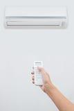 Main avec à télécommande dirigé sur le conditionneur Image stock