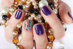 Main avec de beaux ongles manucurés tenant des colliers de perle Images stock