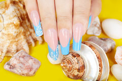 Main avec de longs ongles manucurés et coquilles français artificiels de mer Photos stock