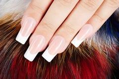 Main avec de longs ongles manucurés français artificiels sur le fond de fourrure Photo stock