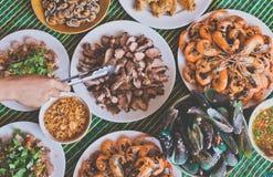 Main avec des beaucoup fruits de mer délicieux avec du porc rôti Photo stock