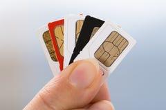 Main avec des cartes de sim de téléphone Images stock
