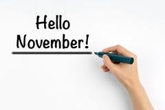 Main avec l'écriture bonjour novembre de marqueur ! Images stock