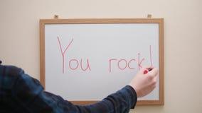 Main avec l'écriture de marqueur et inscription d'effacement que vous basculez sur le conseil blanc banque de vidéos