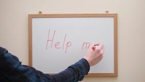 Main avec l'écriture et l'inscription Hepl de marqueur d'effacement je sur le conseil blanc clips vidéos