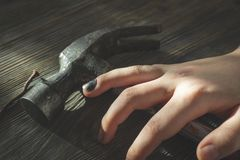 Main avec l'ongle du pouce noirci au-dessus d'un marteau image libre de droits