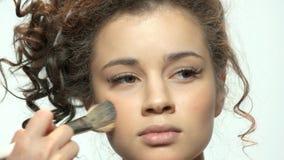 Main avec la brosse appliquant le maquillage banque de vidéos