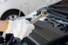 Main avec la clé réparant le moteur de voiture Photographie stock libre de droits
