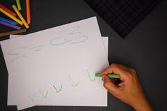 Main avec la craie de couleur sur le papier Photos libres de droits