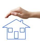 Main avec la maison bleue de concept Photos stock