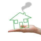 Main avec la maison verte de concept Image stock