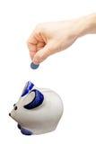 Main avec la pièce de monnaie au-dessus d'une tirelire sur le fond blanc Image stock