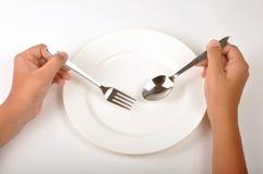 Main avec la plaque de dîner photo libre de droits