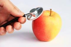 Main avec la pomme de consultation de stéthoscope Images stock