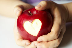 Main avec la pomme, qui a coupé le coeur Image stock