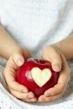 Main avec la pomme, qui a coupé le coeur Photographie stock libre de droits