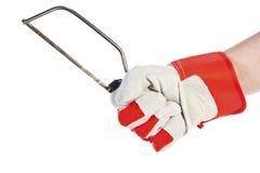 Main avec la scie à métaux de fixation de gant de protection Photos libres de droits