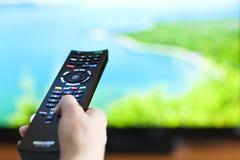 Main avec la télévision à télécommande photos libres de droits