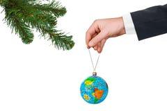 Main avec la terre et l'arbre de Noël Photographie stock libre de droits