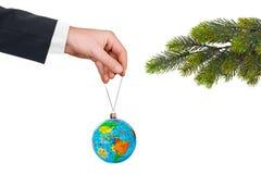 Main avec la terre et l'arbre de Noël Photographie stock