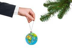Main avec la terre et l'arbre de Noël Images libres de droits