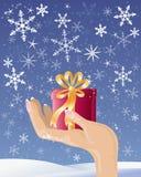 Main avec le cadeau de Noël Image stock