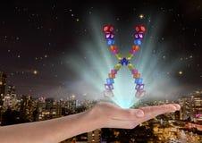 main avec le chromosome d'icônes d'application au-dessus et avec des lumières bleues Devant la ville brouillée la nuit Photographie stock libre de droits