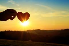 Main avec le coeur de papier au lever de soleil Photographie stock
