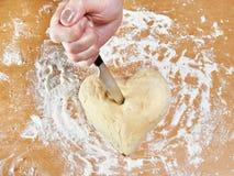 Main avec le coeur frappé par couteau de la pâte Images stock
