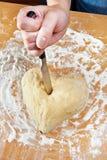 Main avec le coeur frappé par couteau de la pâte Image stock