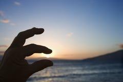 Main avec le coucher du soleil. Image libre de droits