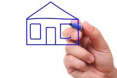Main avec le crayon lecteur dessinant une maison Images stock
