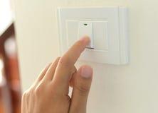 Main avec le doigt sur l'interrupteur de lampe, images stock