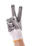 Main avec le gant de travail affichant le signe de victoire ou de paix Images stock
