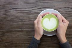 Main avec le latte de thé vert sur le fond en bois photo libre de droits
