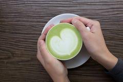 Main avec le latte de thé vert sur le fond en bois photos libres de droits