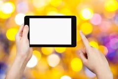 Main avec le PC de comprimé sur le fond jaune et bleu Photographie stock libre de droits