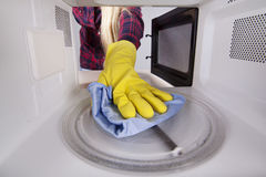 Main avec le plan rapproché de chiffon à l'intérieur de la micro-onde Photos stock