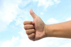 Main avec le pouce sur le fond de ciel Image libre de droits