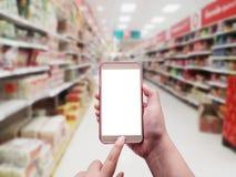 Main avec le smartphone dessus brouillé à l'arrière-plan de magasin Images stock