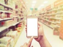 Main avec le smartphone dessus brouillé à l'arrière-plan de magasin Photo libre de droits