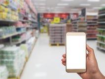 Main avec le smartphone dessus brouillé dans le magasin Image libre de droits