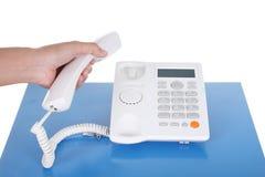 Main avec le téléphone sur une table illustration stock