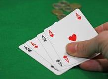 Main avec le tisonnier des as sur un jeu de table Images libres de droits