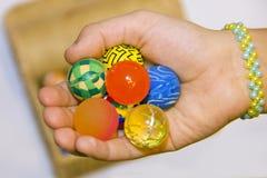 Main avec les boules colorées et boîte complètement de boules colorées image libre de droits