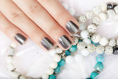 Main avec les ongles manucurés métalliques gris et les bracelets colorés images stock