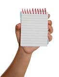 main avec un cahier Image stock