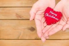 Main avec un coeur avec le Joyeux Noël de message Photographie stock libre de droits